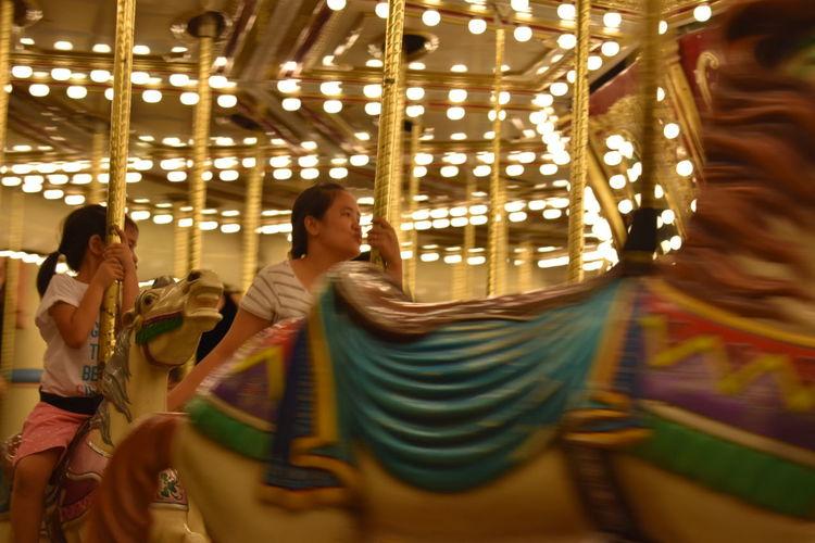 Children Enjoying On Carousel Horses At Amusement Park