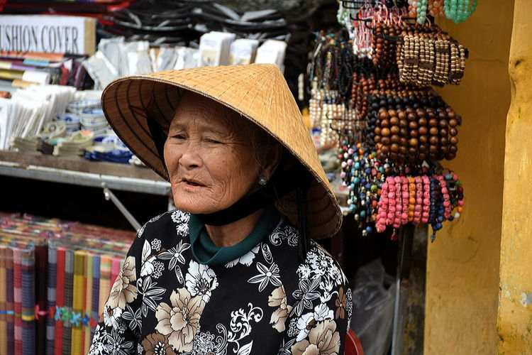 Elderly Lady selling souvenirs to tourist in Hội An, Vietnam Adult Adults Only Business Consumerism Day Hat Market Market Lady In Vietnam Market Stall Market Vendor Mature Adult One Person Outdoors People Portrait Real People Retail  Selling Senior Adult Sombrero Souvenir Vendor Store Straw Hat Sun Hat Traditional Clothing