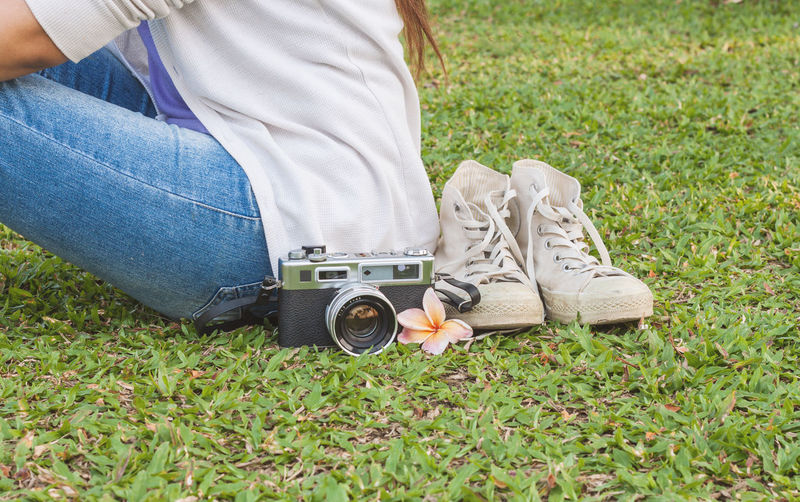 Midsection Of Woman Sitting By Vintage Camera And Sneakers On Grassy Field