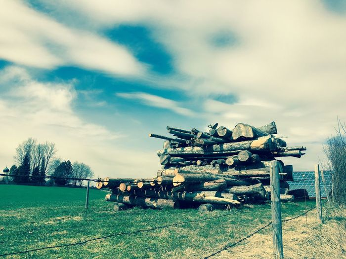 Stack Of Logs On Field Against Sky