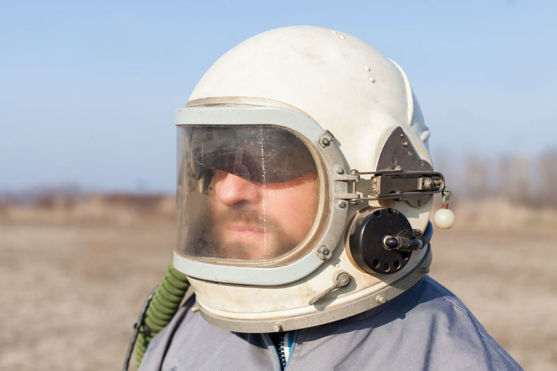 combat pilot preparing for taking flight Astronaut Desert Soldier Standing Aviation Close-up Combat Day Explorer Field Flight Headshot Headwear Helmet Men Military Obscured Face Outdoors Oxygen Pilot Portrait Preparing Protective Sky Uniform