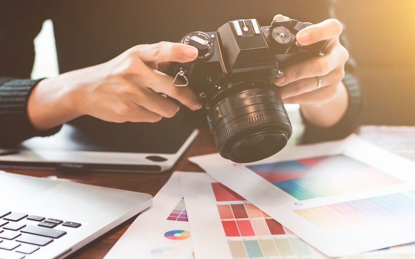 Midsection of design professional holding camera on table