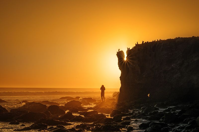 Silhouette Person By Cliff At Beach During Sunset