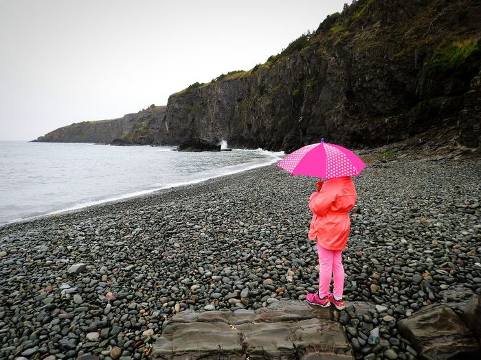 Tiny Umbrella - Big 🎈 Dreams ~ One Person Full Length Outdoors Rear View Beach Childhood Beauty In Nature Cliffs And Sea Waves Rolling In Living In The Moment Nikon Photography Pebbles And Stones Great Grand Daughter! Rainy Days Independent♡ Woman Around The World Newfoundland Looking Into The Future Children Photography Little Girl Morning Mist ReflectingOnTheDay
