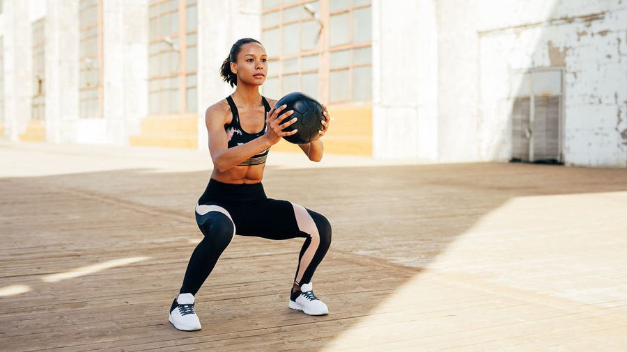 Full Length Of Woman Exercising With Medical Ball Outdoors