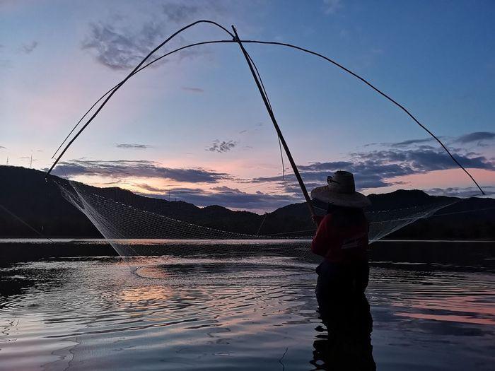 Man fishing in lake against sky during sunset