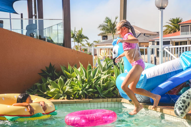 poolside fun with inflatables- young girls in swimsuits having a fun summer day by the pool Pool Swimming Pool Water Leisure Activity Full Length Lifestyles Real People Child Women Nature Day Sunlight Childhood Girls People Swimwear Sitting Outdoors Inflatable