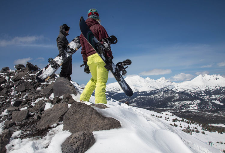 Low Angle View Of Man And Woman Skiing On Snowcapped Mountain