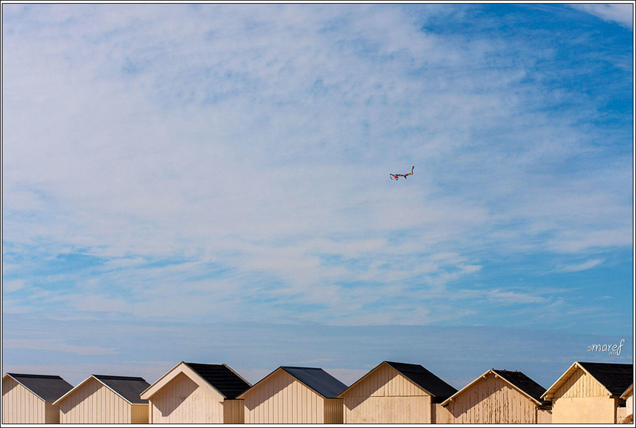 sky, cloud - sky, flying, blue, low angle view, cloud, cloudy, airplane, built structure, mid-air, day, transfer print, air vehicle, outdoors, architecture, transportation, auto post production filter, nature, building exterior, sea