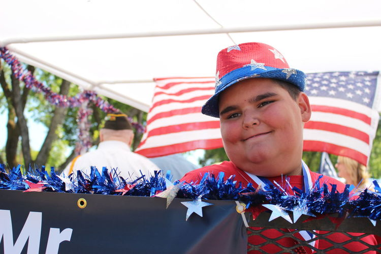 Smiling Boy Looking Away While Standing Against American Flag During Event