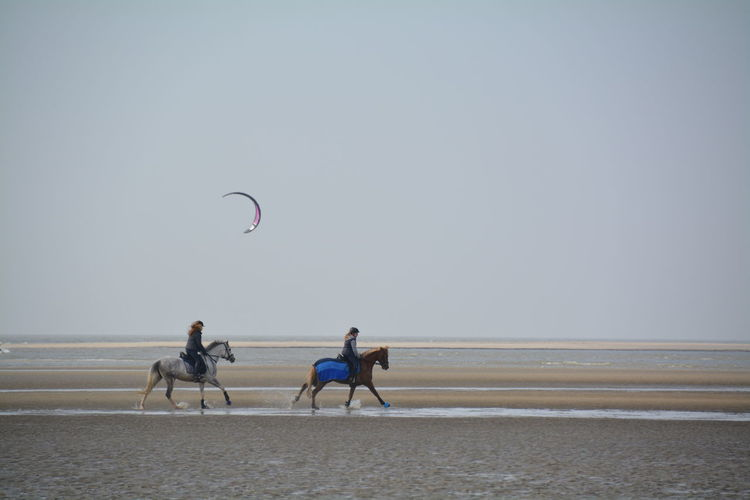 Women riding horses at beach against sky