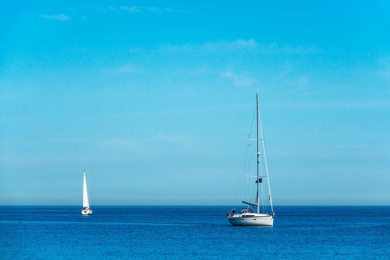 Sailboat Sailing On Sea Against Blue Sky