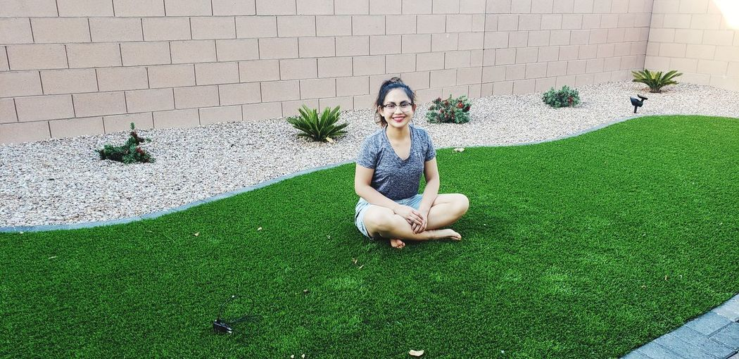 Full Length Portrait Of Smiling Woman Sitting On Turf Against Wall