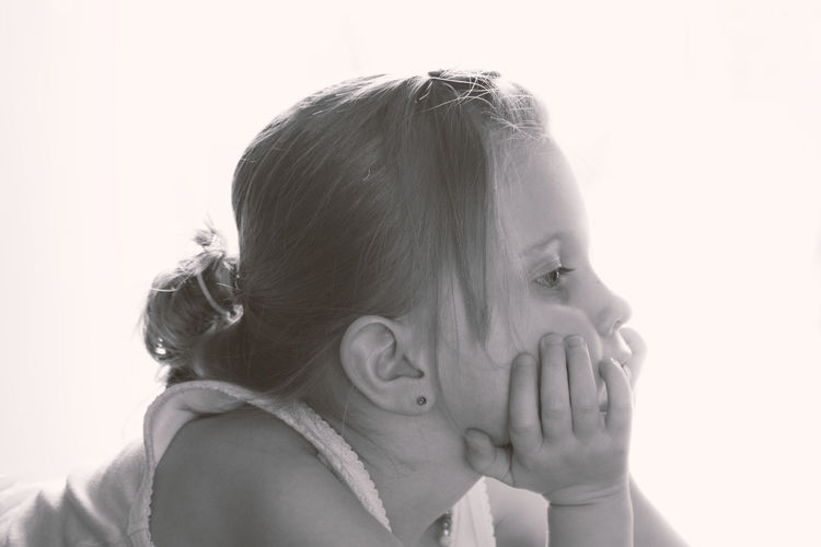 Close-up of cute girl with hand on chin looking away against white background