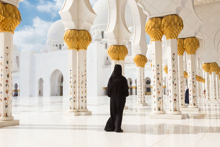 Rear view of woman walking in mosque