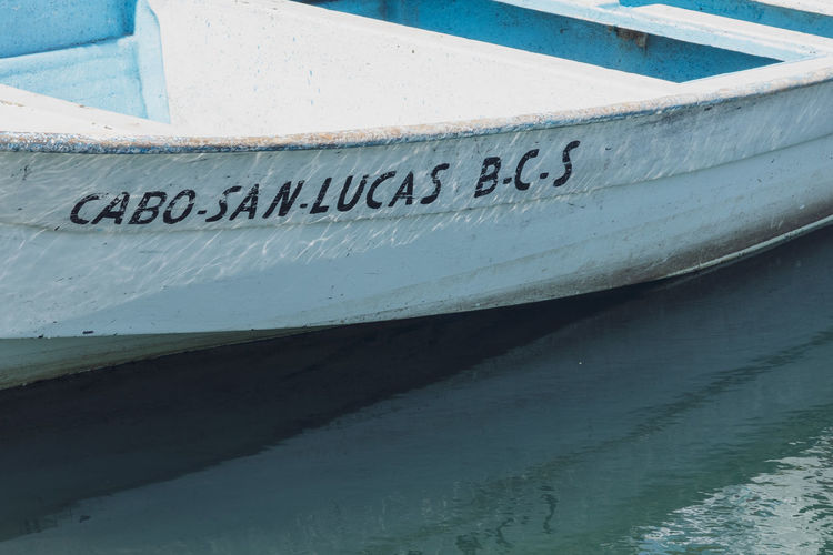 Close-up of text on boat moored in lake