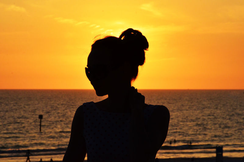 Rear view of silhouette woman standing against sea during sunset