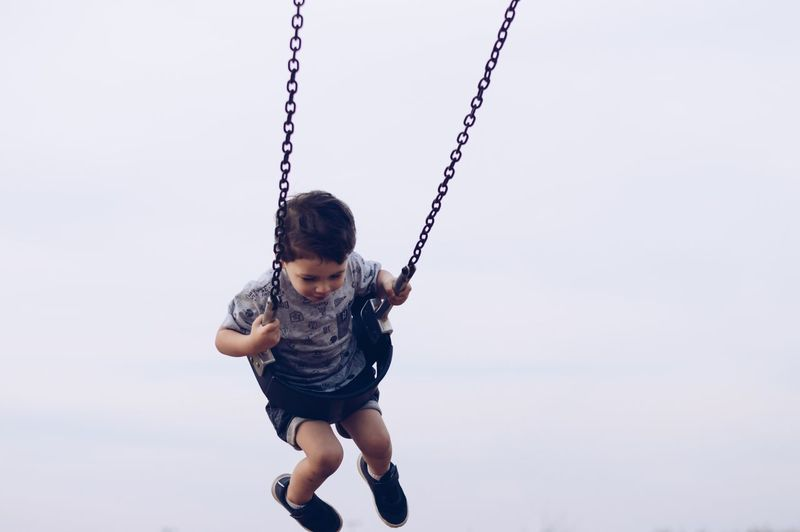 Full length of boy playing on swing against sky