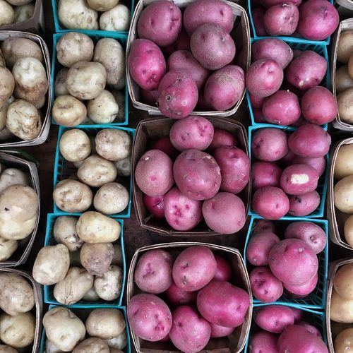 High angle view of potatoes in containers at market for sale