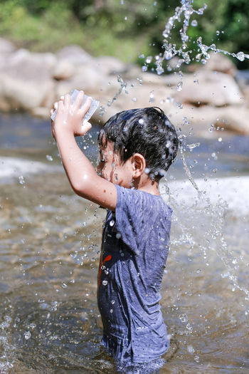 Boys Child Childhood Day Enjoyment Flowing Water Innocence Leisure Activity Lifestyles Males  Motion Nature One Person Outdoors Playing Real People Splashing Spraying Three Quarter Length Water Wet