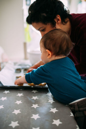 Togetherness Family With One Child Family Matters Cookies Cooking Lifestyles Bonding Sitting Positive Emotion Casual Clothing Women Childhood Child Family Table Two People People Innocence Motherhood Real People Helping Teaching Quality Time