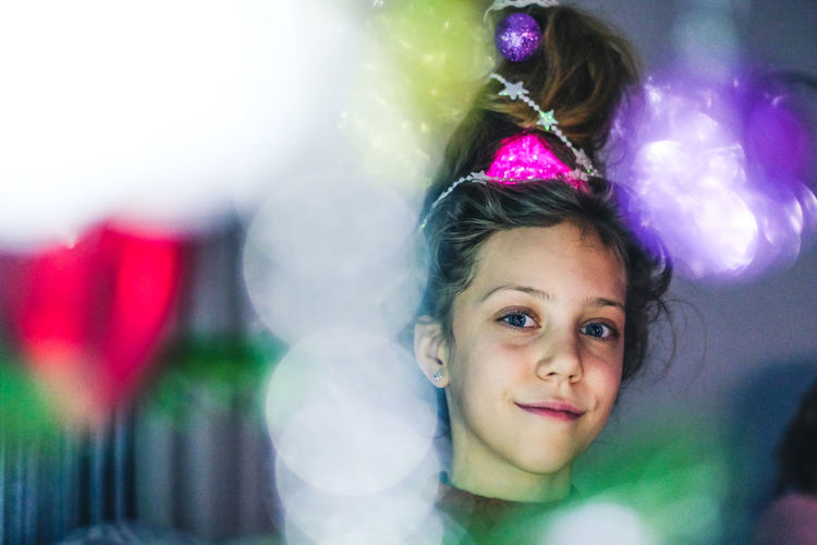 Close-up portrait of smiling girl by illuminated christmas lights