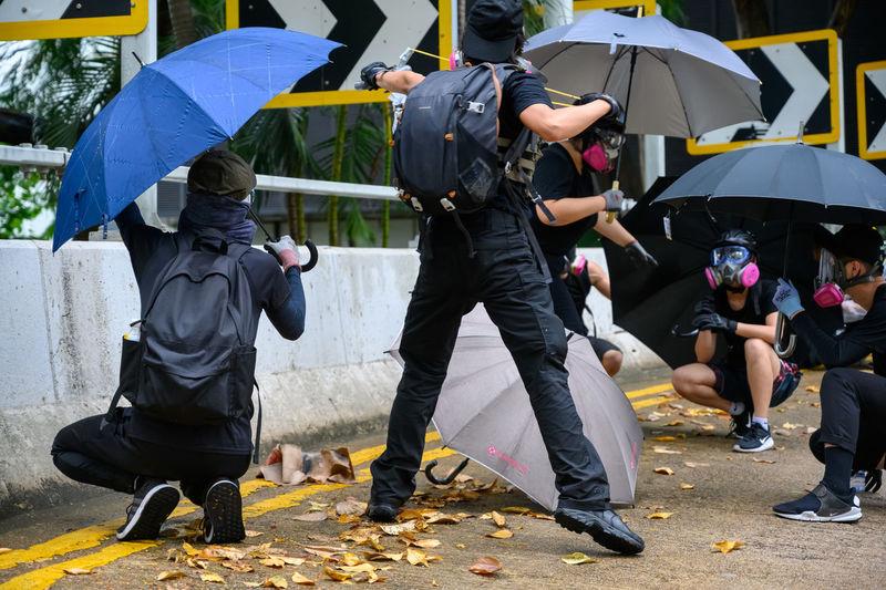 People with masks holding umbrella on street