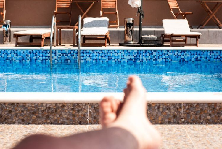 Low section of person resting by swimming pool