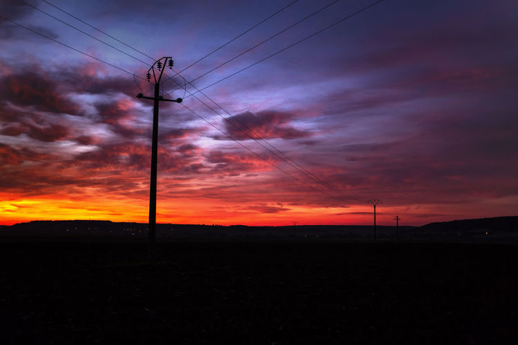 Low angle view of silhouette electricity pylon on field against sky at sunset