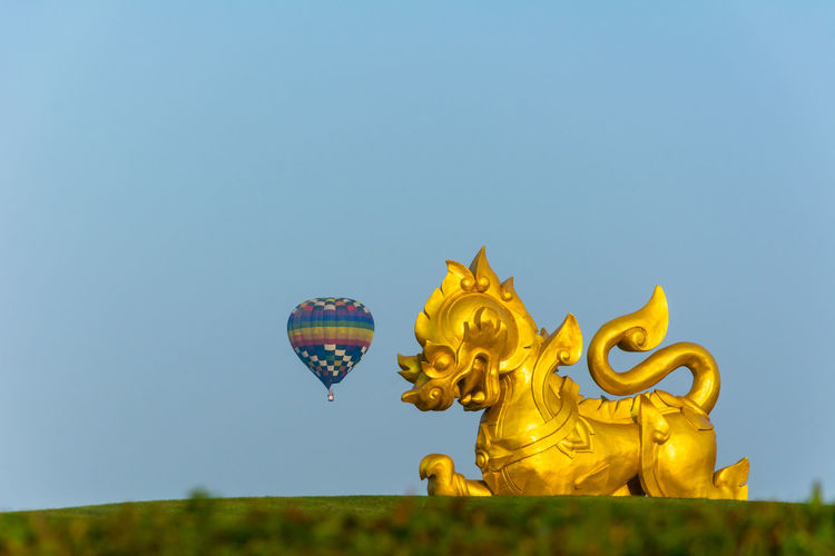 Gold Statue Against Hot Air Balloon Flying In Sky