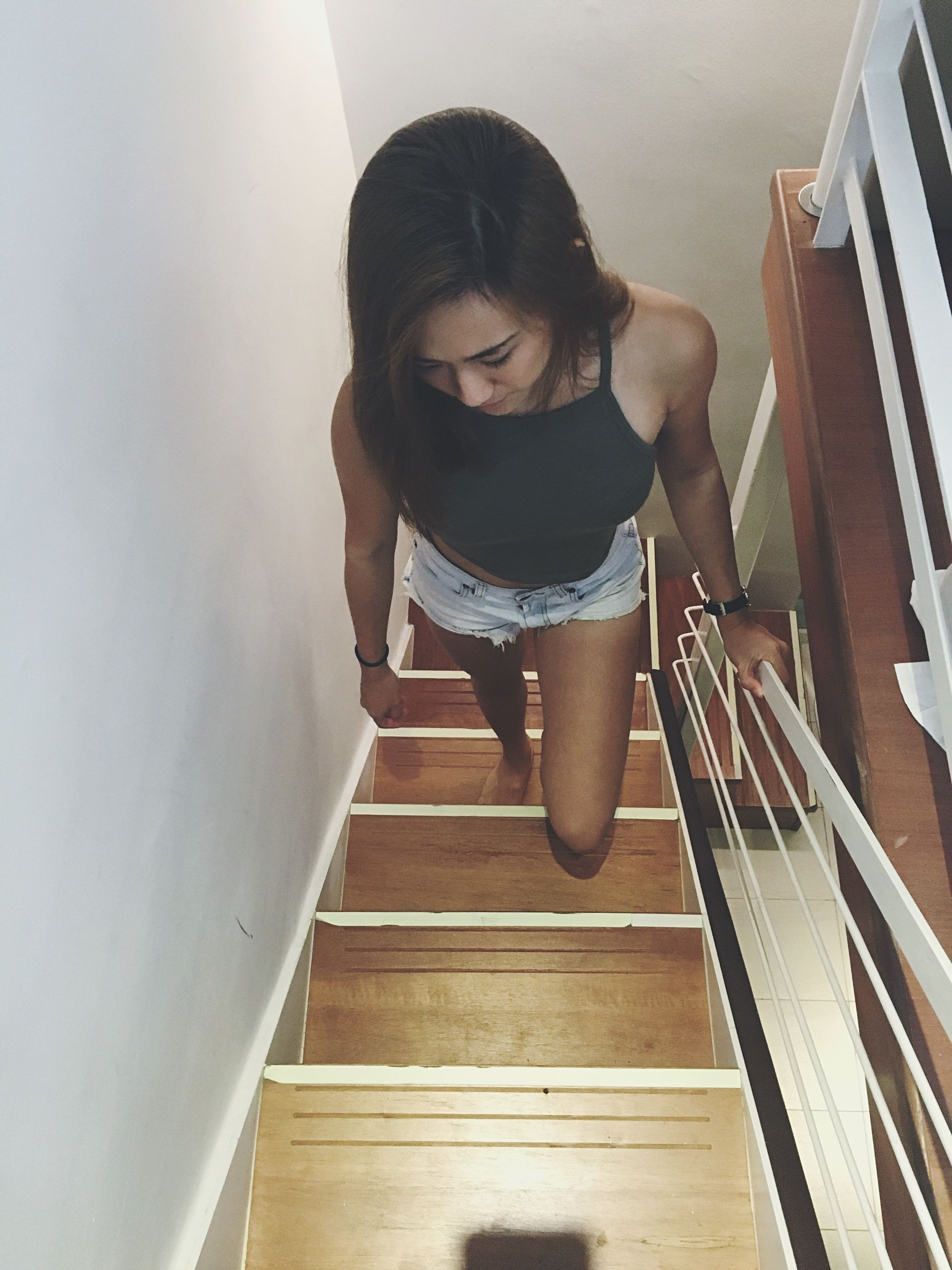 young adult, lifestyles, architecture, built structure, low angle view, indoors, steps, casual clothing, person, standing, leisure activity, staircase, front view, steps and staircases, railing, young women, wall - building feature, building exterior