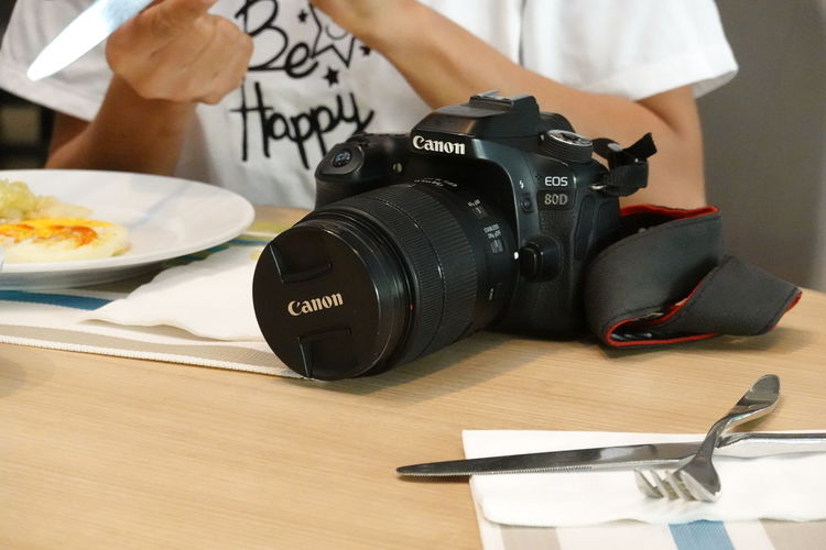 Midsection of woman photographing with camera on table