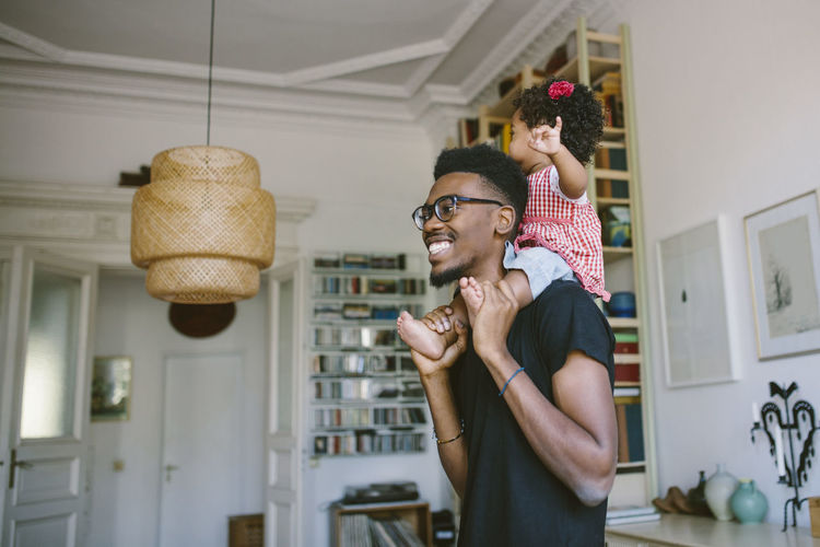 Smiling young man carrying playful daughter at home