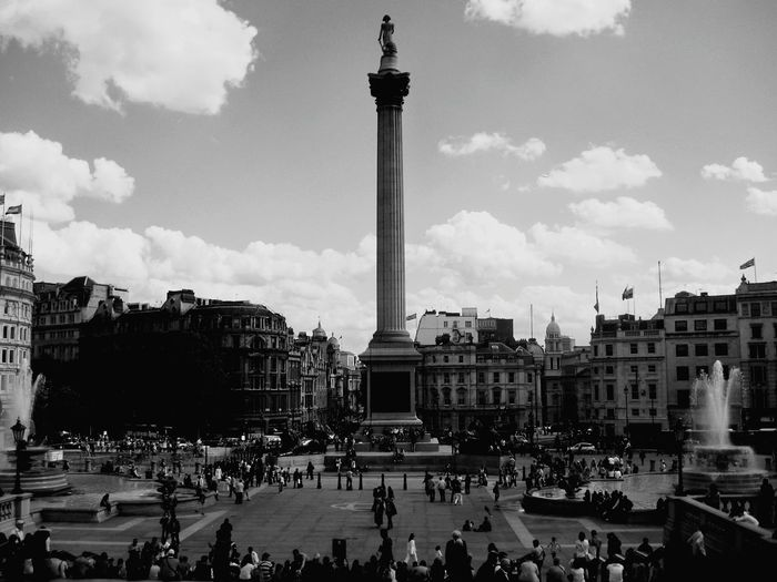 People at trafalgar square in city against sky