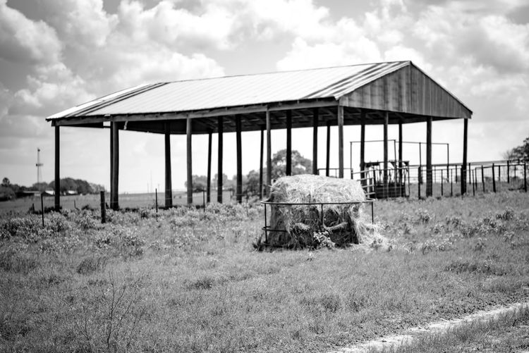 Old barn on field against sky