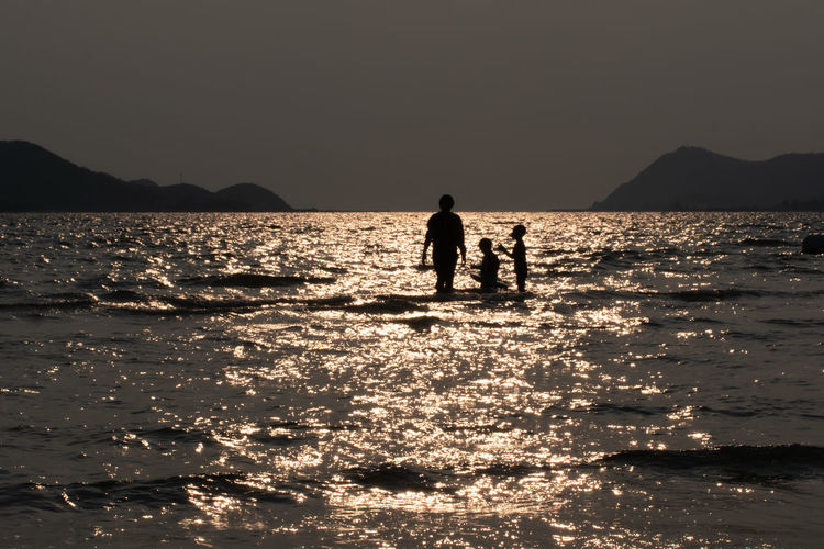 Silhouette men in sea against sky during sunset