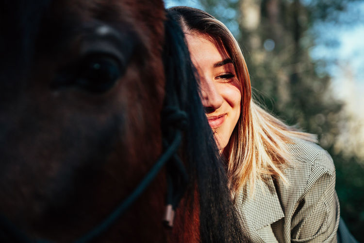 Smiling woman sitting on horse