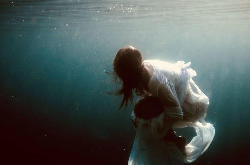 Woman wearing dress swimming in sea