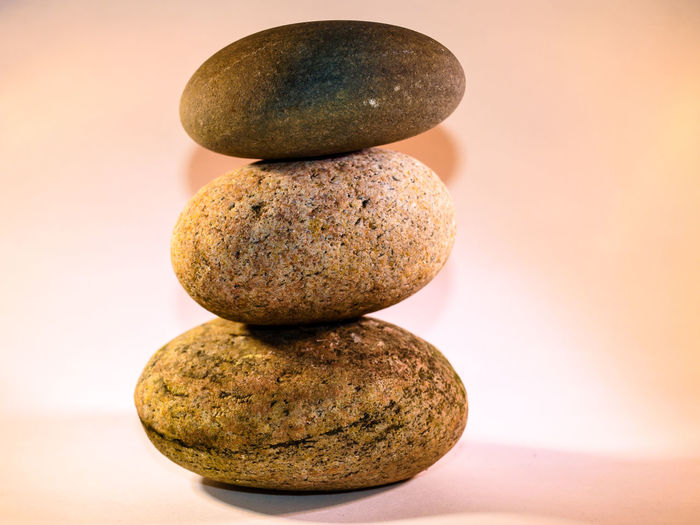 Close-Up Of Stacked Pebbles On Table