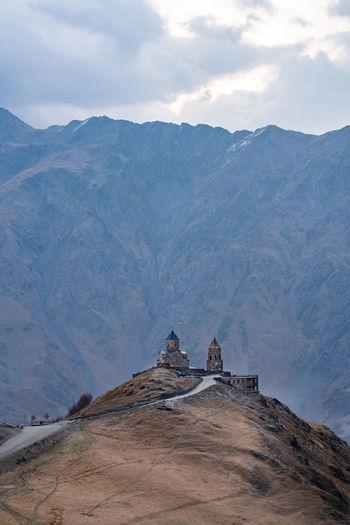 Castle on mountain against cloudy sky