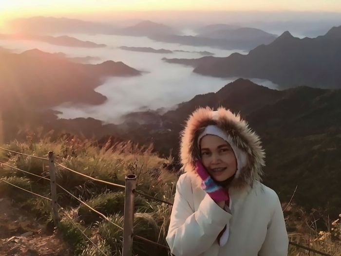 Portrait of smiling woman standing on mountain against sky
