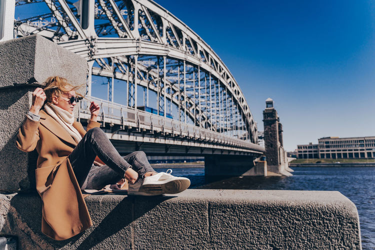 Woman sitting on bridge over river in city against sky