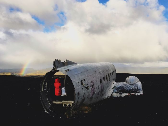 Rear View Of Person Standing In Abandoned Airplane At Beach