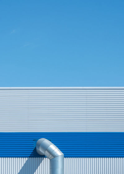 Minimal photograph of a blue warehouse with  shadow and blue skies