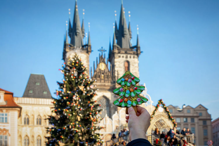 Cropped hand holding christmas tree model against tyn church