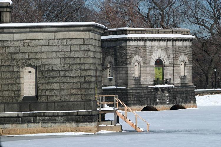Building by frozen central park reservoir during winter