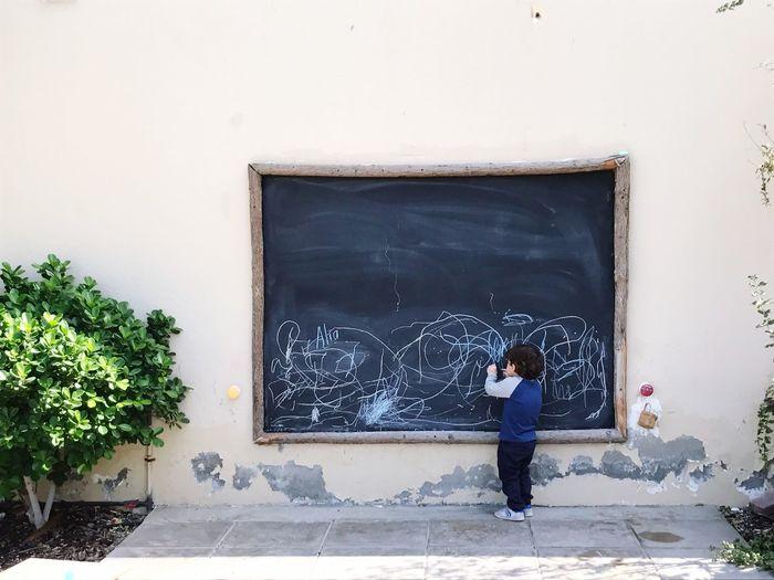 Full Length Of Boy Drawing On Blackboard