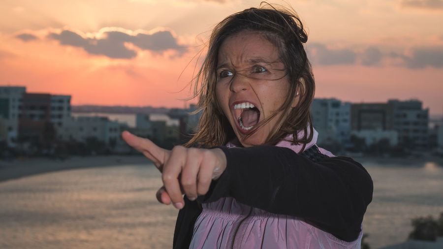 Angry Woman Shouting By Sea In City Against Sky During Sunset