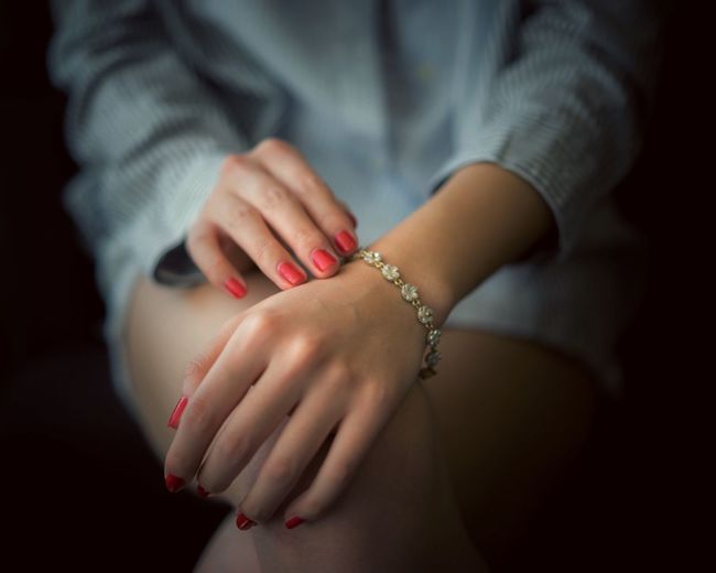 Midsection of woman with red nail polish and bracelet in darkroom
