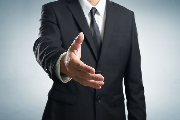 Midsection of businessman reaching for handshake against gray background